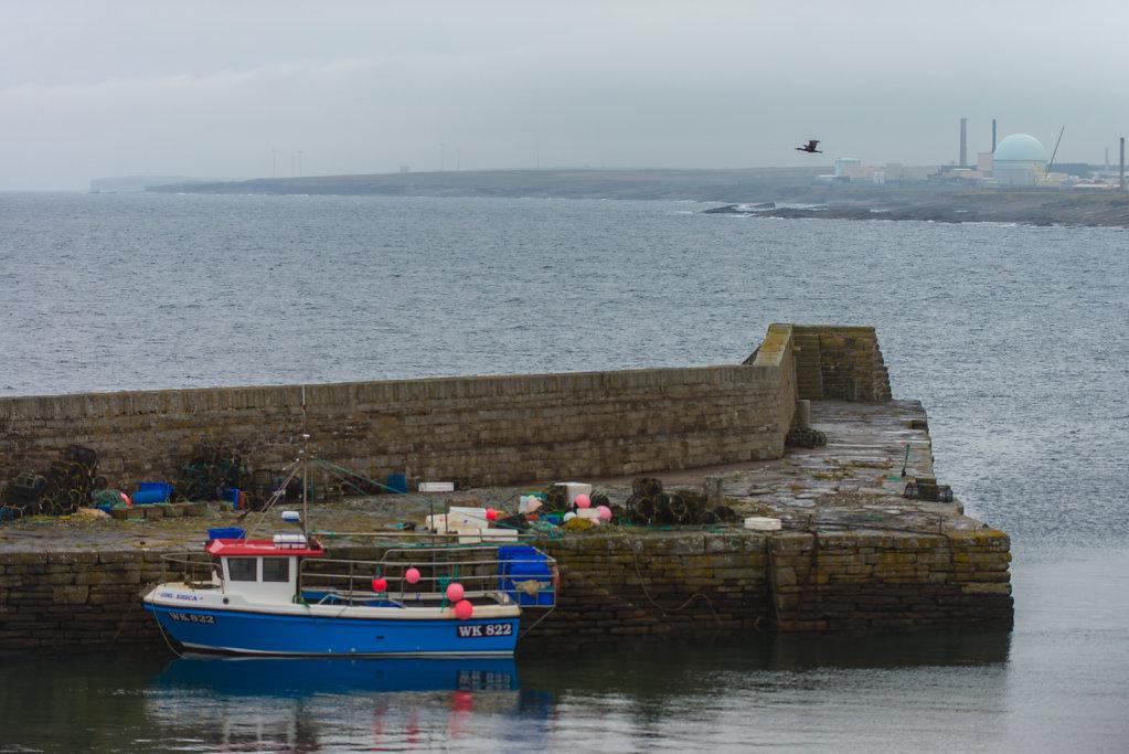 Der kleine Hafen vom Sandside Estate ist fast ausgestorben, der Strand vor dem Atomkraftwerk ist seit einem Zwischenfall radioaktiv verstrahlt und gesperrt. Das Kraftwerk ist nicht mehr in Betrieb und wird zurückgebaut.